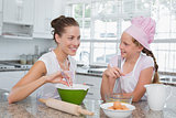 Girl helping her mother prepare food in kitchen