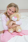Young girl embracing stuffed toy in bed
