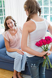 Girl surprising mother with flowers in bedroom