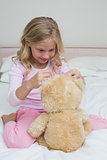 Relaxed girl sitting with stuffed toy in bed