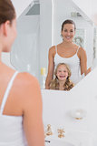 Happy mother and daughter looking at bathroom mirror