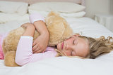 Young girl sleeping with stuffed toy in bed
