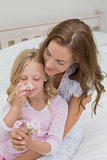Mother and daughter with flowers in bedroom