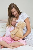 Woman and girl playing with stuffed toy in bedroom
