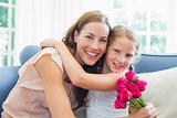 Happy mother and daughter embracing with flowers in living room