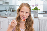 Portrait of a young girl having breakfast in kitchen