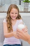 Happy young girl receiving a glass of milk