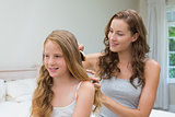 Beautiful young woman brushing little girl's hair