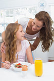 Mother looking at daughter while having breakfast in kitchen