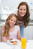 Mother with daughter having breakfast in kitchen