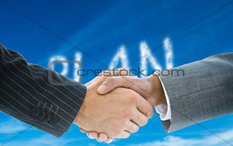 Composite image of business handshake against plan