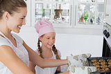 Girl looking at mother remove cookies from oven