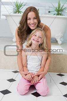 Portrait of smiling mother and daughter in the bathroom