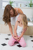 Mother and pretty daughter sitting in bathroom