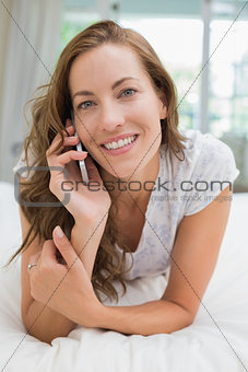 Beautiful smiling young woman using mobile phone in bed