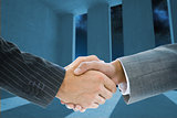 Composite image of business handshake against light shining