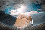 Composite image of business handshake against wall