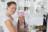 Girl with mother removing cookies from the oven