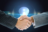 Composite image of business handshake against shiny light bulb