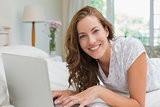 Beautiful smiling woman using laptop in bed