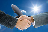 Composite image of business handshake against plane