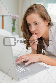 Beautiful serious woman using laptop in bed