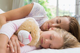 Girl and mother sleeping peacefully with stuffed toy