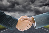 Composite image of business handshake against storm