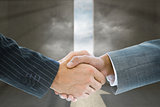 Composite image of business handshake against door