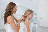 Woman braiding cute little girl's hair in bathroom