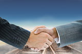 Composite image of business handshake against railway