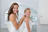 Woman braiding cute little girl's hair in bathroom