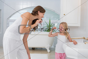 Girl brushing teeth as she looks at her mother