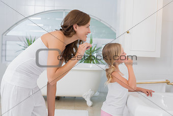 Little girl brushing teeth with mother
