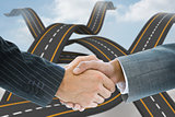 Composite image of business handshake against road