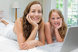 Happy mother and daughter using laptop in bedroom