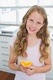 Smiling young girl with a sweetlime slice in kitchen