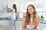 Girl having breakfast with mother in background at kitchen