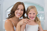 Close-up of mother with daughter brushing teeth