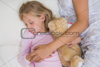 Girl and mother sleeping peacefully with stuffed toy in bed