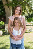 Happy woman embracing daughter from behind at park