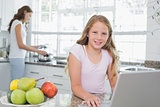 Daughter using laptop with mother cooking food in background at kitchen