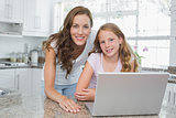 Portrait of a happy mother and daughter using laptop in kitchen