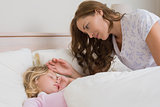 Mother watching girl as she sleeps peacefully in bed