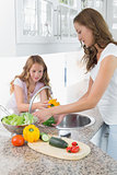 Girl helping her mother to wash vegetables in kitchen