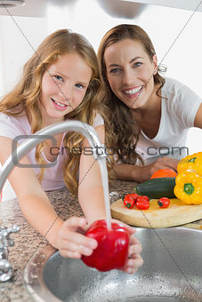 Portrait of young girl helping her mother to wash vegetables