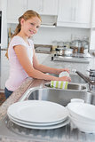 Portrait of a girl washing utensils in kitchen