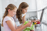 Girl helping mother to cut vegetables in kitchen