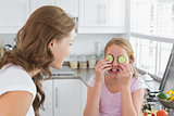 Woman looking at girl keep cucumber slices on eyes in kitchen