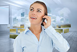 Composite image of smiling businesswoman looking upwards while on her phone